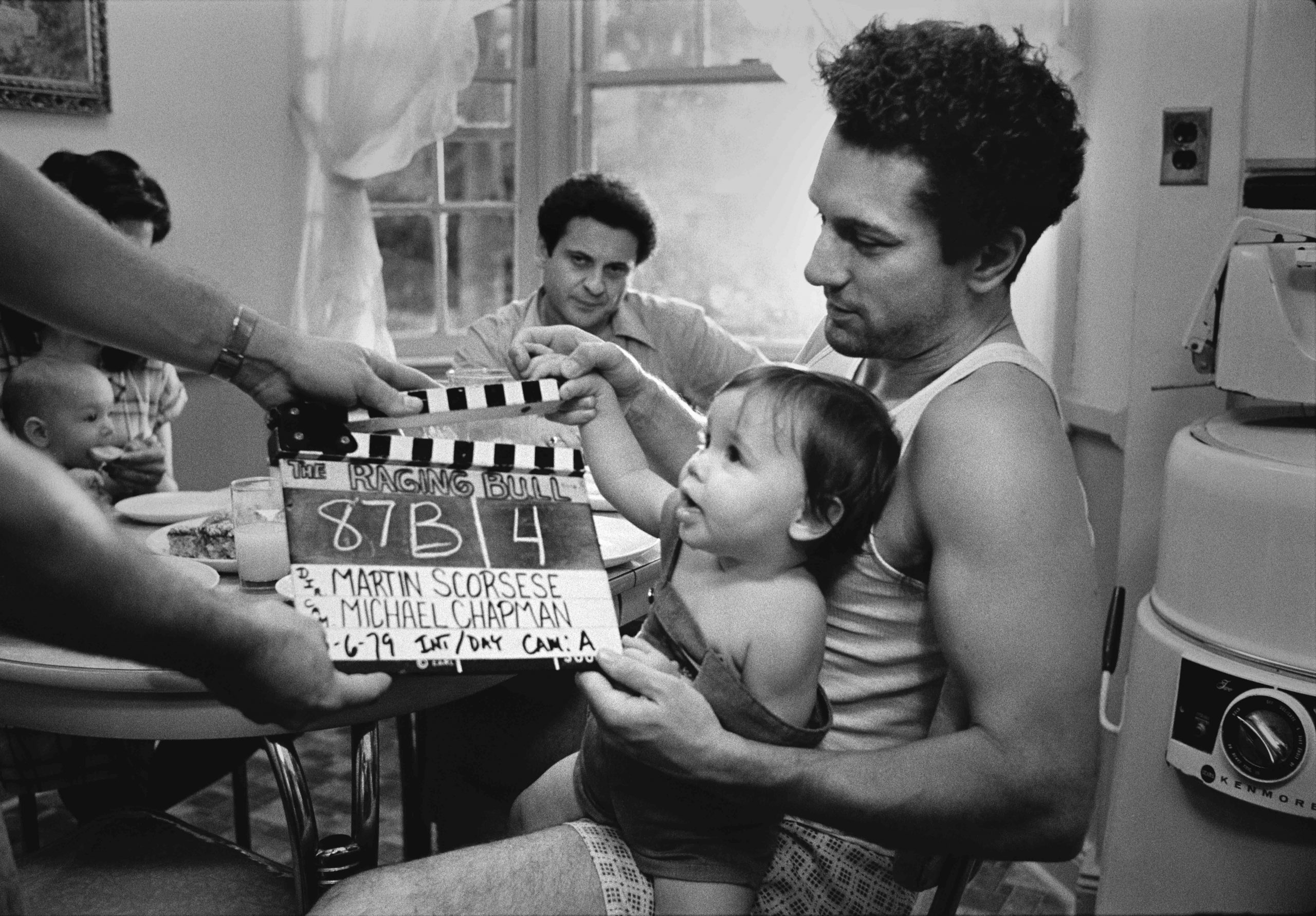 Robert De Niro with baby and clapperboard on the set of Raging Bull (1980)